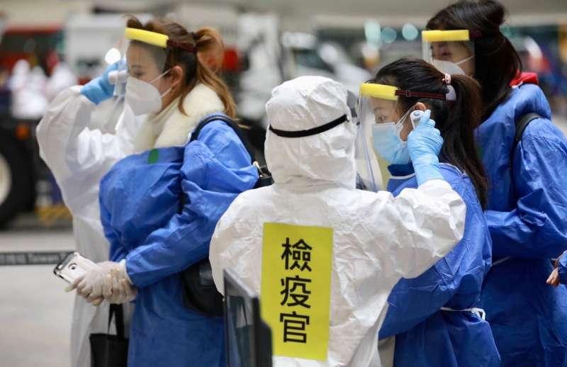第二批武漢包機華航專機於0310晚上抵達桃園機場旅客正接受檢疫人員量測體溫.(疾病管制署疫情指揮中心提供)