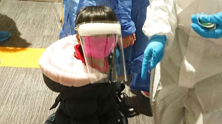 3月10日第2次武漢包機返台國人中有許多年幼兒童,防疫人員貼心手工製作符合小朋友體型的防護面罩,以保護兒童全程安全。(圖/中央流行疫情指揮中心提供)