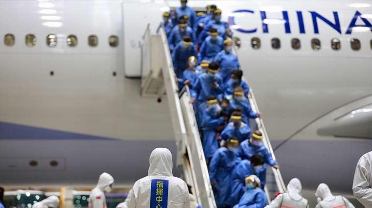 穿著防護衣、配戴口罩的返台國人陸續下機,配合相關檢疫措施。(圖/中央流行疫情指揮中心提供)