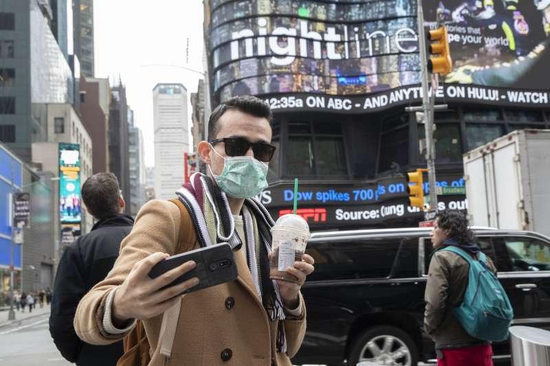 美國新冠肺炎(武漢肺炎)疫情持續升溫,紐約時報廣場上的遊客也戴起口罩(AP)