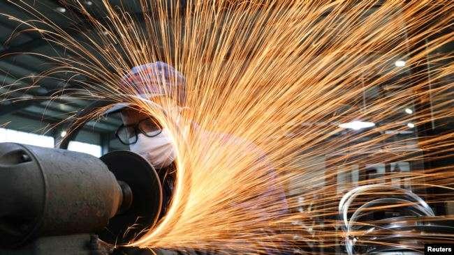 2020年3月2日,浙江杭州市一名戴著口罩的工人在生產自行車輪子鋼圈的生產線上工作。(美國之音/Reuters)