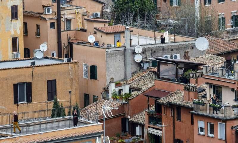 米蘭的民眾在自家屋頂為義大利的醫護人員鼓掌加油。(美聯社)