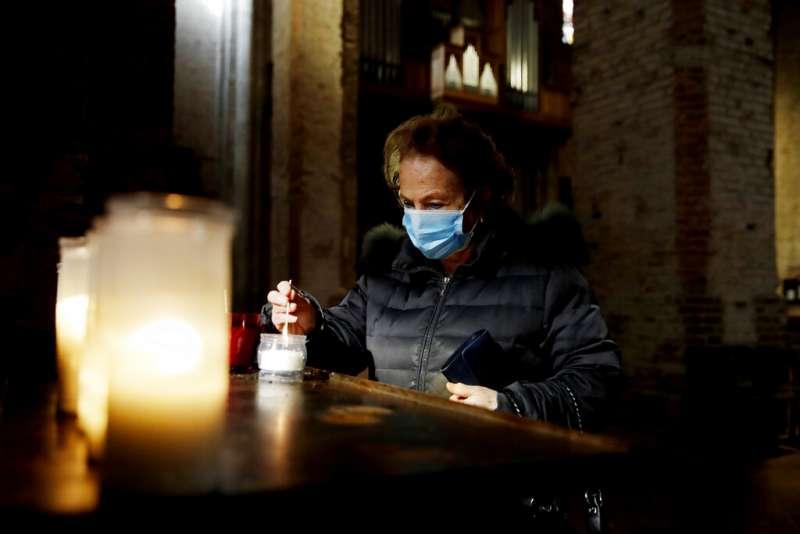 義大利疫情肆虐,聖新伯立咸隱修院裡一位民眾戴著口罩參加禮拜活動。(美聯社)