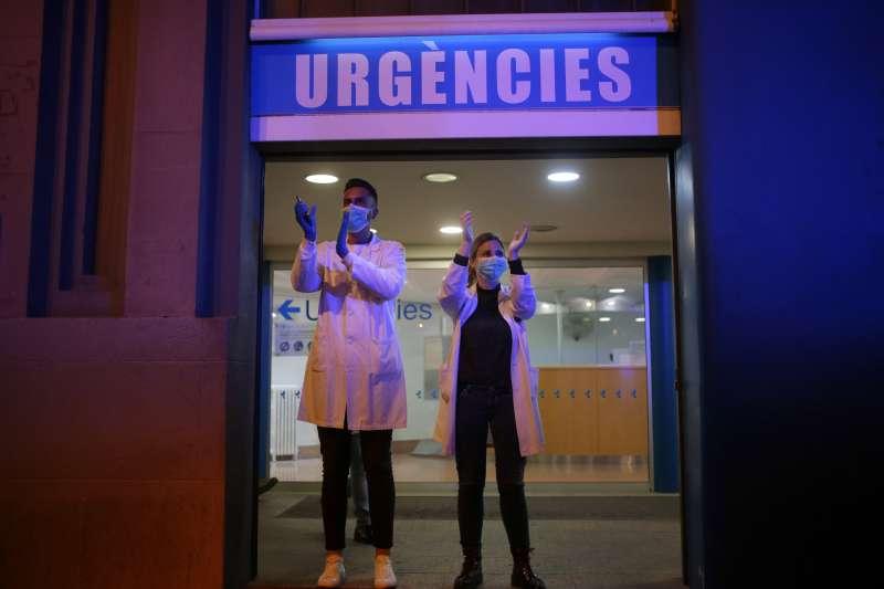 西班牙新冠肺炎疫情愈發嚴峻,為醫療體系帶來沉重負擔,巴塞隆納有醫護人員出面向支持民眾致謝(AP)