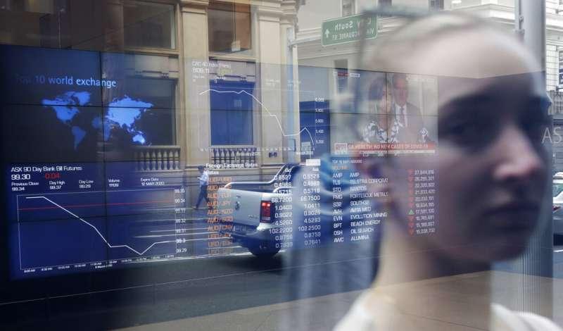 一位雪梨民眾正在澳洲證交所外觀看股市行情。(美聯社)