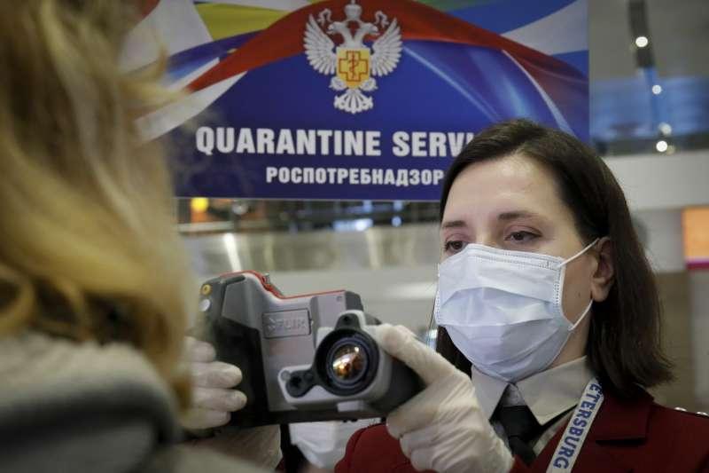 武漢肺炎:聖彼得堡普爾科沃機場的工作人員為返國旅客量測體溫(AP)