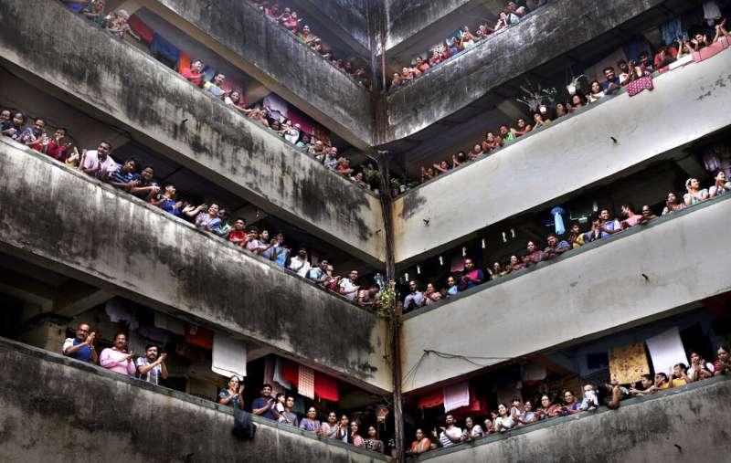 禁足期間民眾竟走上陽台拍手為抗議工作人員加油。(AP)