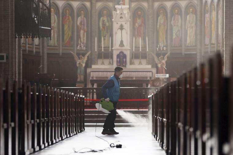 2月26日,南韓一名工作人員在首爾天主教明洞聖堂消毒(美聯社)