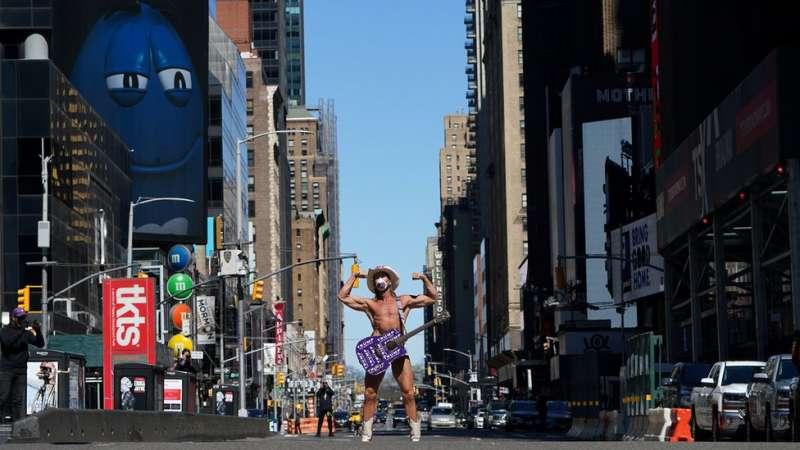一位赤身戴有口罩的年輕人在空蕩蕩的紐約時代廣場演唱。