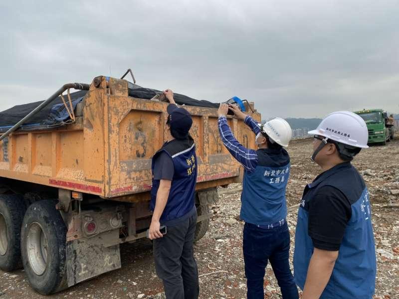 兩輛樽鴻土資場業者違法置放的營建廢棄物卡車,被環保局當場查扣。(圖/新北市工務局提供)