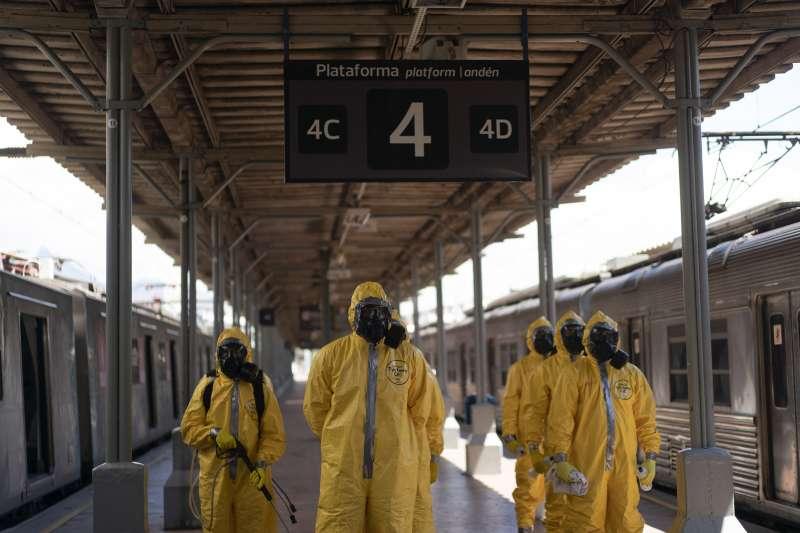 里約中央車站月台,軍人準備進入列車消毒。(美聯社)