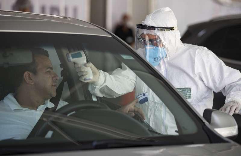 聖保羅市郊,醫護人員為駕駛民眾測量體溫。(美聯社)