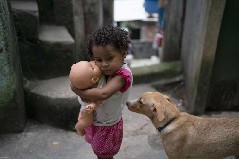 武漢肺炎疫情在全球蔓延,窮人受到嚴重衝擊。圖為巴西里約熱內盧貧民窟的一名小女孩抱著心愛的娃娃(美聯社)