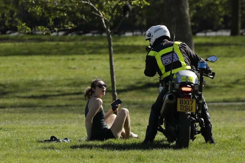 新冠肺炎疫情侵襲英國,警察勸導在公園內曬日光浴的民眾返家(AP)