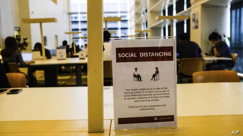 3月16日,新加坡國家圖書館提醒民眾保持社交安全距離(美聯社)