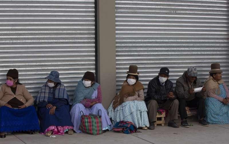 武漢肺炎疫情衝擊經濟,西班牙政府擬推無條件基本收入(UBI)。圖為玻利維亞民眾戴著口罩排隊領生活補助金。(AP)