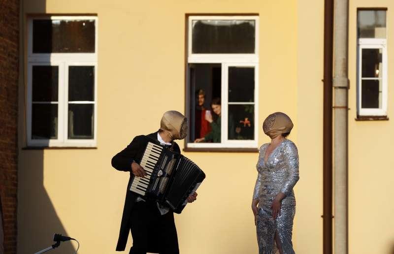 新冠肺炎肆虐歐洲,捷克疫情逐漸趨緩,街頭藝人為遵守禁足令在家的民眾表演(AP)