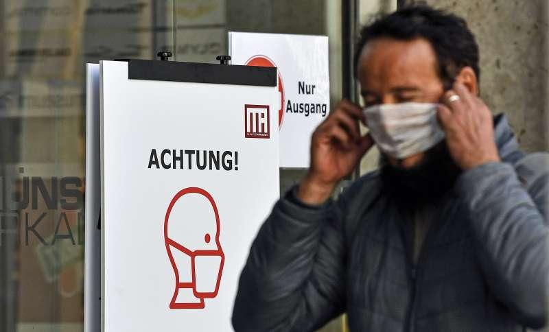 新冠肺炎疫情侵襲全球,德國一間商場要求顧客配戴口罩。(AP)