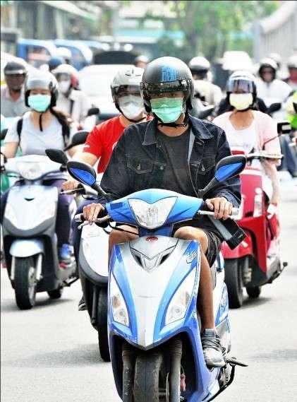 肺炎防疫期間,民眾配戴口罩自行騎乘機車,避免搭乘大眾運輸工具造成疫情傳染。(圖/臺中市政府環保局)