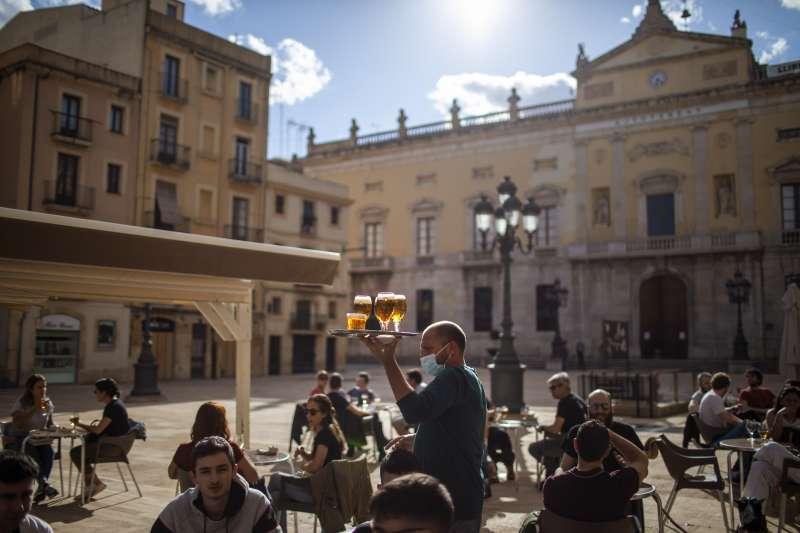 西班牙疫情高峰過去,各城鎮開始逐步解禁,民眾在陽光下聚會、小酌。(AP)