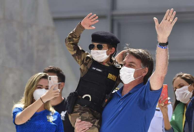 巴西總統博索納羅無視社交隔離建議,週日還是跟支持者、孩童近距離互動。(AP)