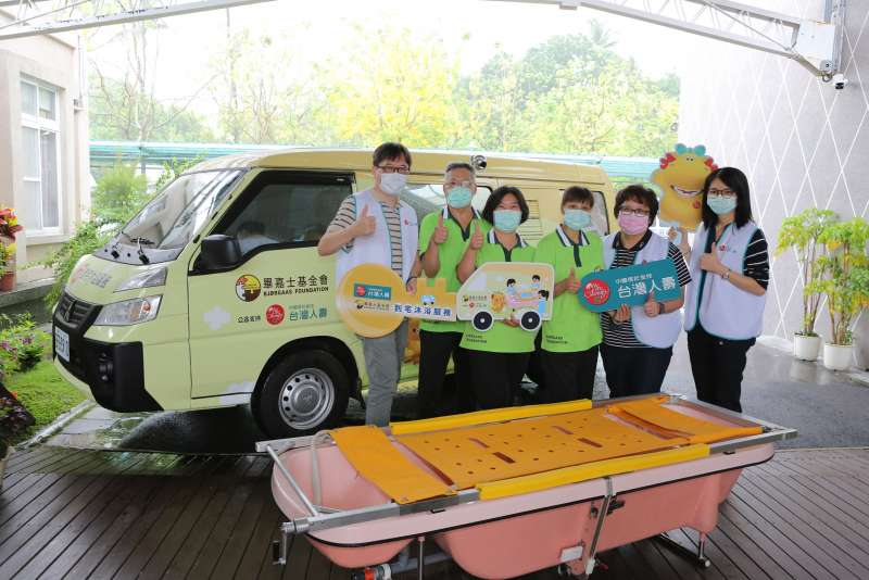 21日由台灣人壽協理王韋凱(左一)與畢嘉士三人一組的到宅沐浴服務專業團隊於到宅沐浴新車及設備前大合照。(圖/台灣人壽提供)