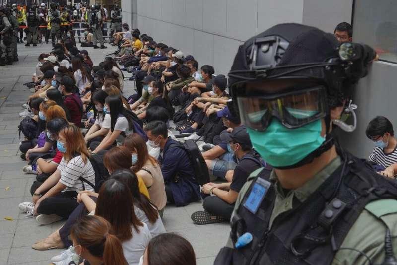 2020年5月27日,香港的反政府示威者在銅鑼灣被警察逮捕後坐在地上。(美聯社)