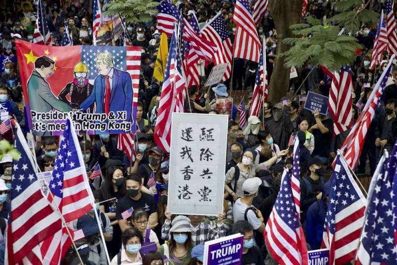 香港去年抗爭,群眾拿著美國國旗,期待華府介入。(美聯社)