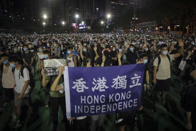 香港民眾在維多利亞公園悼念六四受難者,並且高舉「香港獨立」的標語、以及「五大訴求缺一不可」的手勢。(美聯社)
