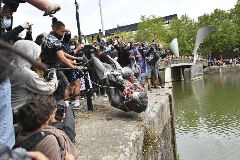 全球掀起反種族歧視抗議浪潮,在英國布里斯托,示威者將17世紀奴隸商科斯頓(Edward Colston)的雕像拆除並丟入河中。(AP)