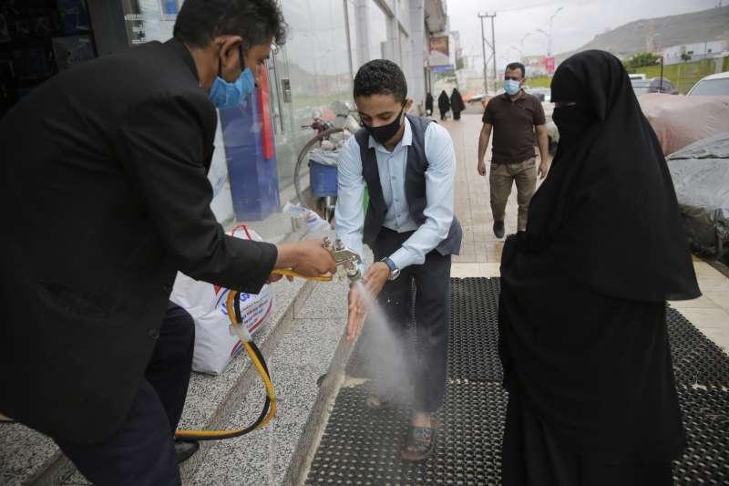 葉門新冠肺炎疫情攀升,圖為葉門首都沙那的購物中心,正在替客人消毒手部。(AP)