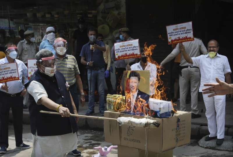 中印衝突引發新一波反中浪潮。圖為新德里示威民眾焚燒習近平照片。(美聯社)