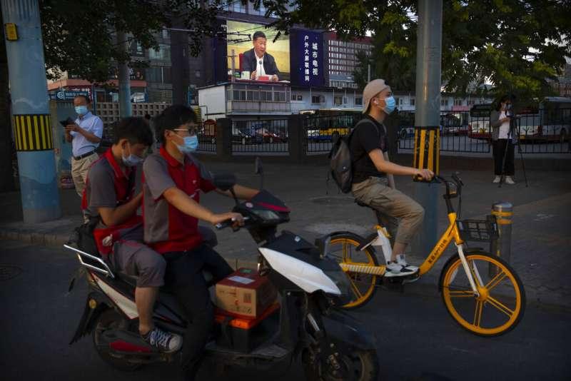 習近平發表談話的畫面出現在北京街頭。(美聯社)