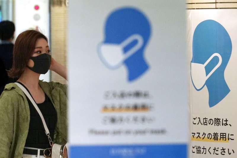 東京街頭仍可看到提醒民眾配戴口罩的宣傳海報。(美聯社)