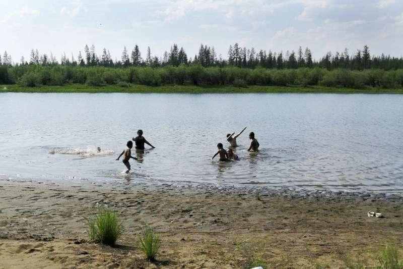 2020年6月,俄羅斯西伯利亞東北部維科揚斯克鎮(Verkhoyansk)創下攝氏38度高溫紀錄,當地兒童泡在湖中消暑。(AP)