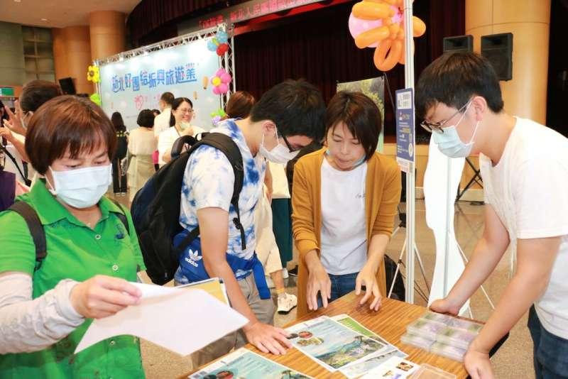 旅行業者在活動現場向民眾說明烏來IG網美一日遊的活動內容。(圖/李梅瑛攝)