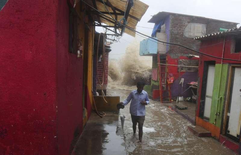 印度雨季導致暴洪,大水正要衝進一處窄巷。(AP)