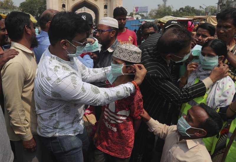 防疫志工協助民眾戴上口罩。新冠疫情期間,印度中低階層居住環境擁擠,難以落實社交隔離。(AP)