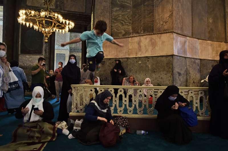 土耳其伊斯坦堡的聖索菲亞(Hagia Sophia)正式從博物館轉型為清真寺,調皮的小男孩正跳進禮拜區域。(AP)