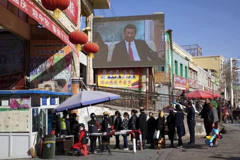 新疆和田市的居民在安全檢查站排隊接受檢查,準備進入和田市集。後方的大螢幕上正在播放中國國家主席習近平的新聞。(美聯社)