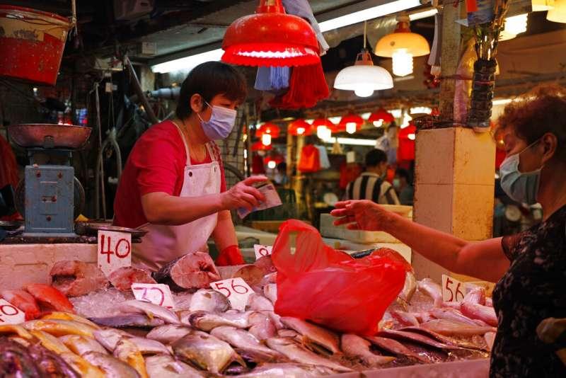 香港連日新增病例破百,民眾出外購物仍戴口罩以免遭到感染。(美聯社)