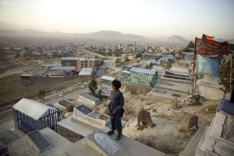 一名在阿富汗喀布爾市郊公墓賣水的少年,在等待顧客時站在墳墓上遠眺。(美聯社)