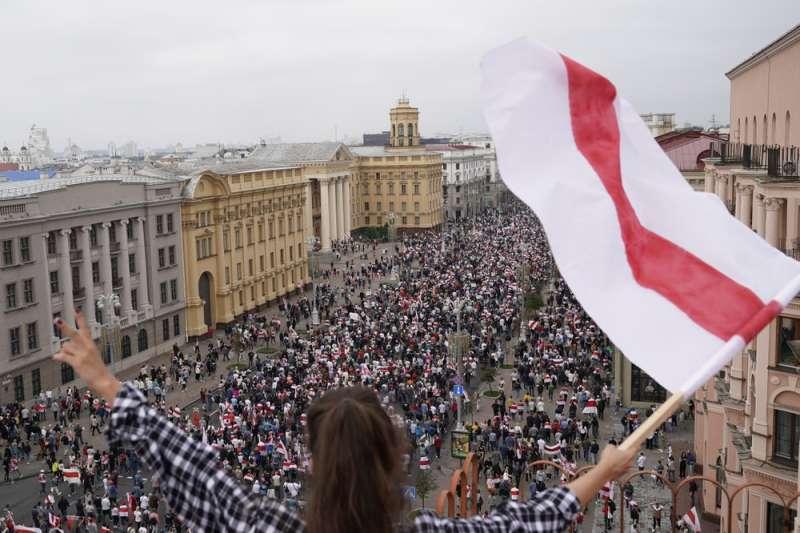 8月23日,大批白羅斯民眾在首都明斯克的獨立廣場示威抗議。一名女子在高處揮舞著抗議的旗幟(美聯社)