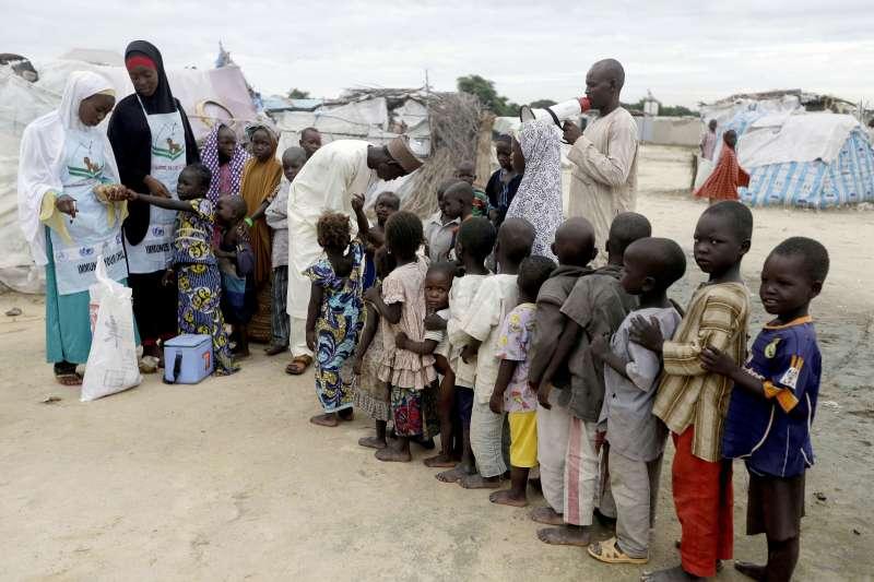 WHO宣布非洲已根除野生脊髓灰質炎(俗稱「小兒麻痺症」)病毒,圖為排隊接受口服疫苗的奈及利亞兒童。(AP)