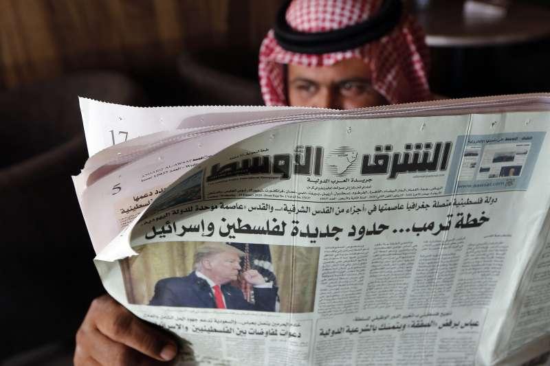 沙烏地阿拉伯的咖啡館內,一名男子看的報紙標題寫著阿拉伯聯合大公國(UAE)宣布與以色列建交。(AP)