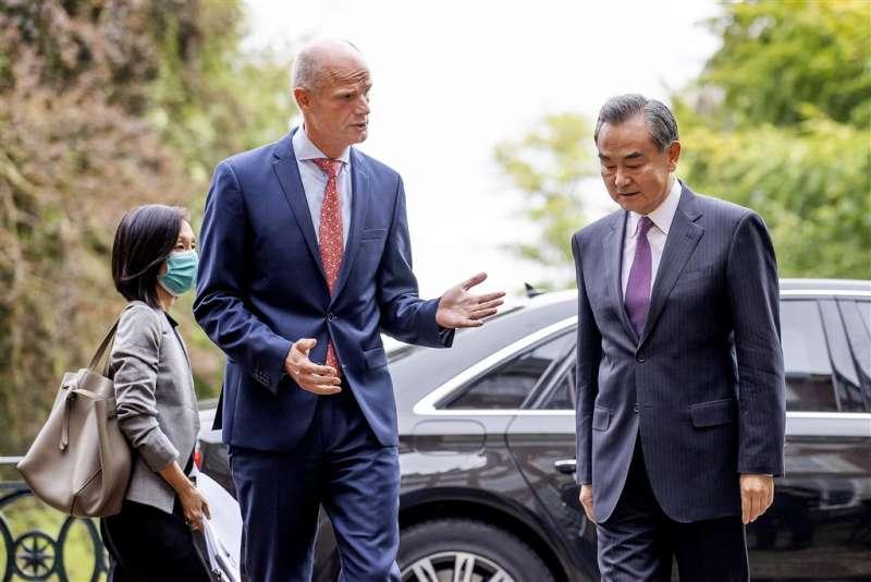 中國外長王毅(前右)24日開始訪歐之行,26日訪問荷蘭時,外長布洛克(前左)當面表示對北京箝制新疆維吾爾人及香港自由的關切。(美聯社)