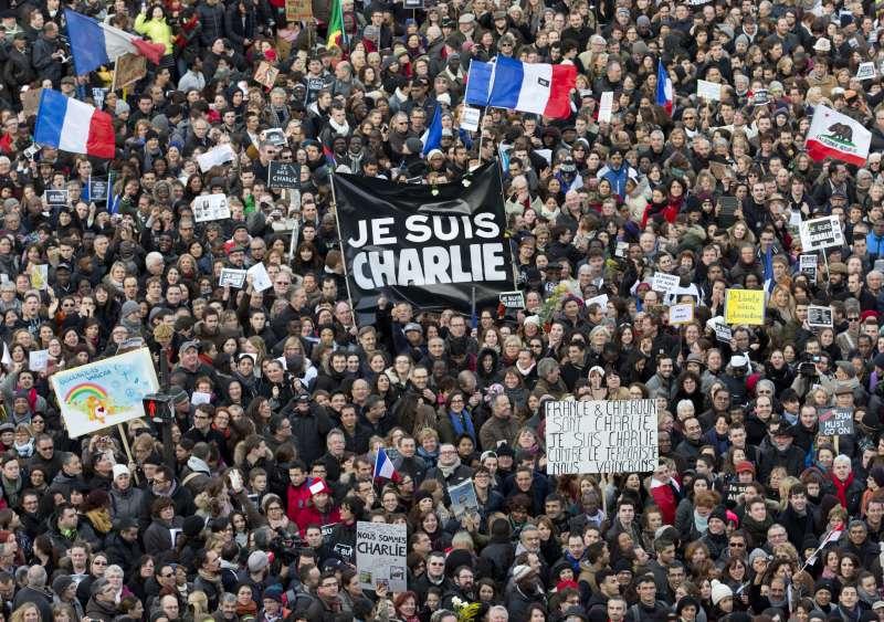2015年法國諷刺刊物《查理週刊》槍擊案,巴黎與全球各地群眾聲援,高舉「我是查理」。(AP)