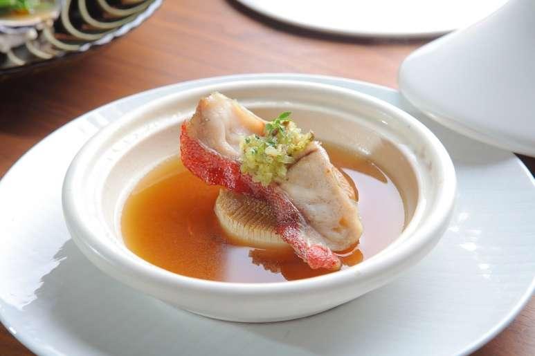 4紅石斑塔吉鍋以台東的現撈紅石斑為食材,湯底以花蓮蜜筍熬煮,口感鮮甜,置於源自於北非的塔吉鍋,可讓蒸氣保留食物鮮甜美味。(圖/Taiwan Tatler)