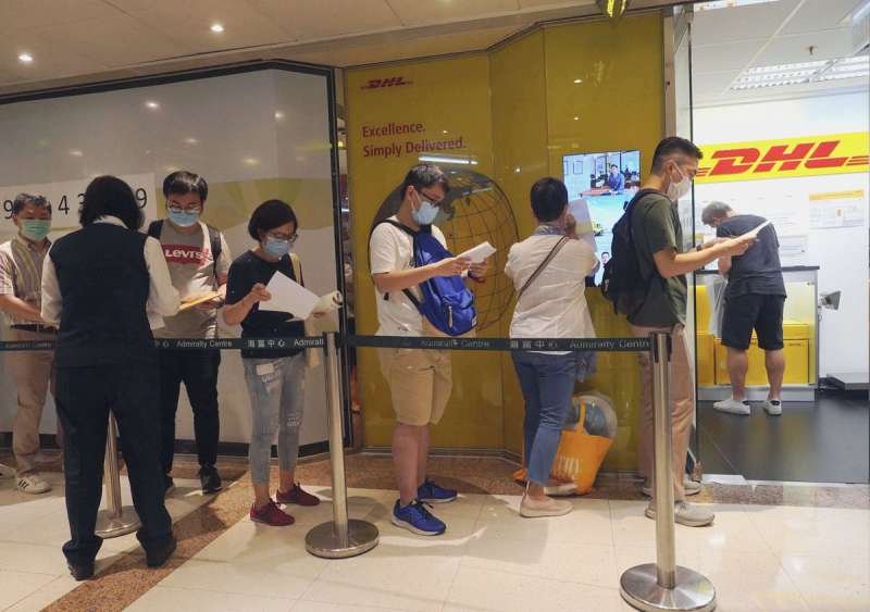憂國安法持續侵蝕香港自治,大批港人在快遞公司外排隊寄交申請BNO的文件。(美聯社)