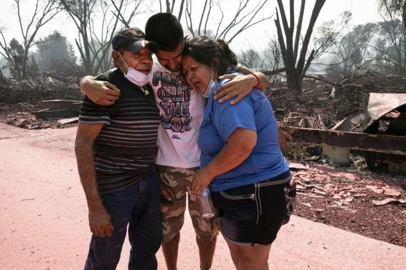 美國奧勒岡州大火蔓延,房屋被燒毀的家庭相擁而泣。(AP)